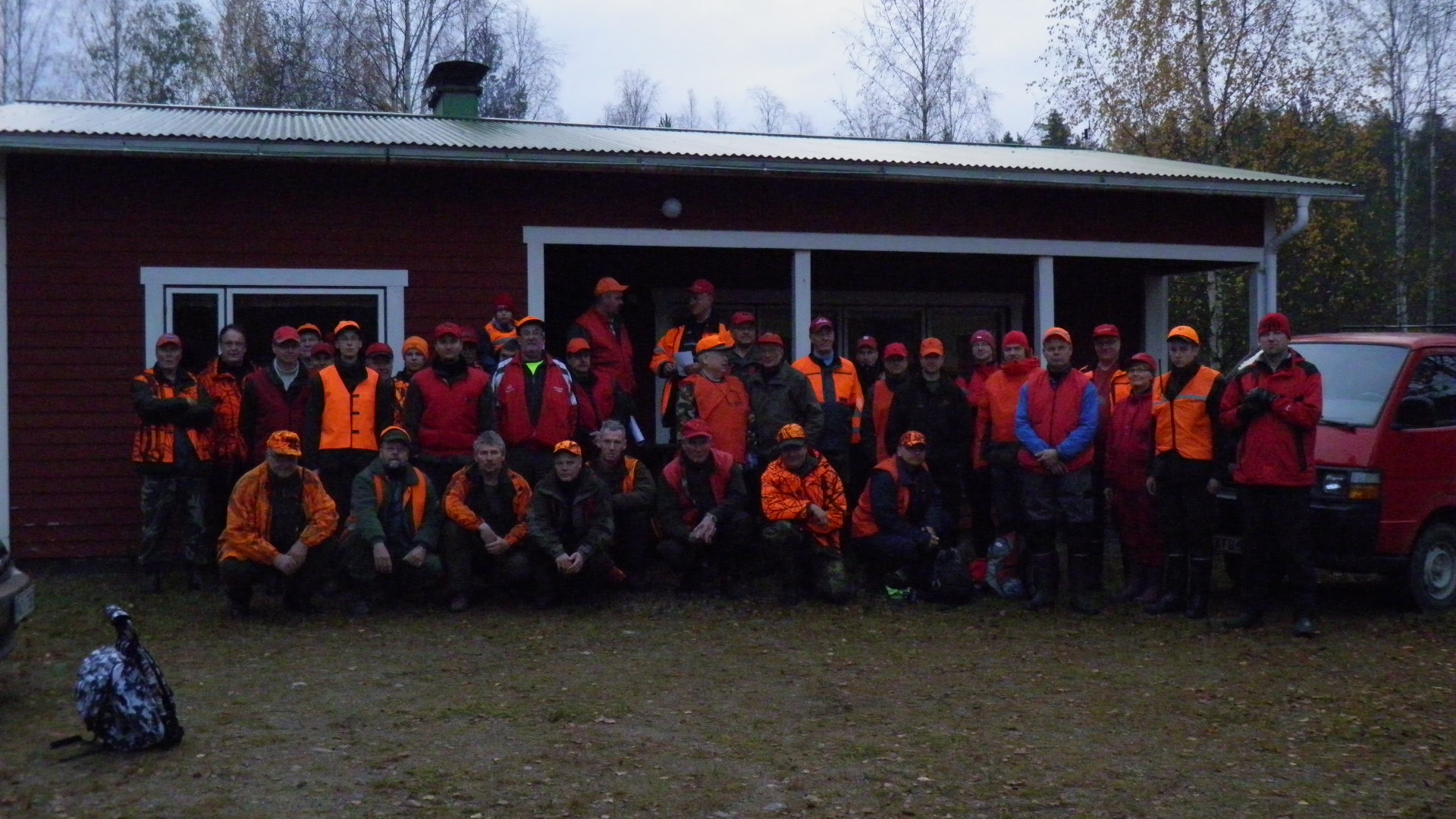 Hirviporukka metsästymajan edustalla.