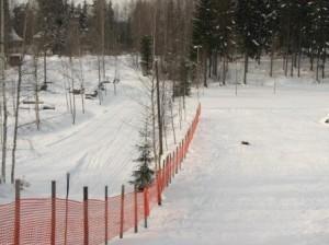 Hiihtoladun ja mäenlaskurinteen välissä on talvisin aita